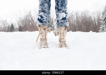 Close up of mid adult womans legs covered in snow - Stock Photo