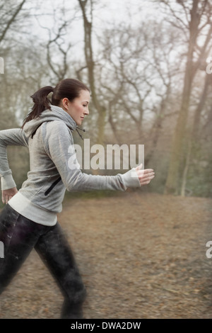 Young woman running through forest - Stock Photo