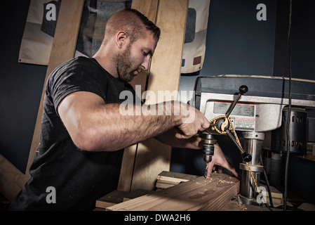 Male carpenter drilling wooden plank in workshop - Stock Photo