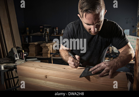 Male carpenter measuring wooden plank with set square in workshop - Stock Photo