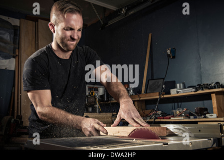 Male carpenter using a rotary saw in workshop - Stock Photo