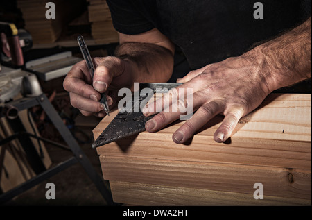 Close up of male carpenter using set square in workshop - Stock Photo