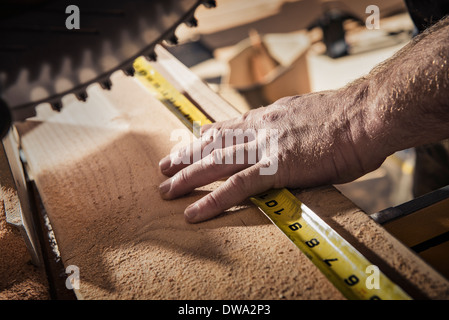 Close up of male carpenter using tape measure in workshop - Stock Photo