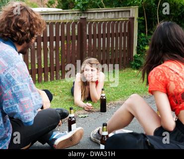 Friends sitting in garden drinking beer - Stock Photo