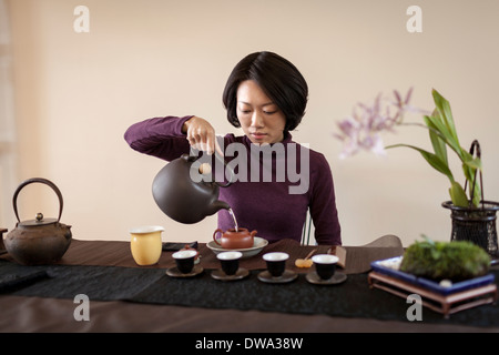 Mid adult woman performing traditional Chinese tea ceremony - Stock Photo