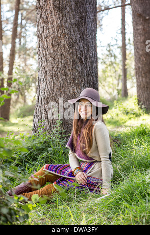 Portrait of young woman in forest, smiling - Stock Photo