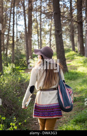 Young woman wearing hat in forest - Stock Photo