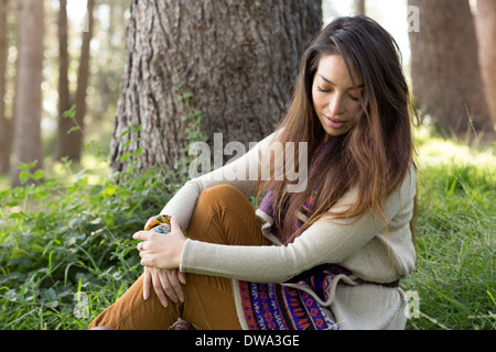 Portrait of young woman in forest, looking down - Stock Photo