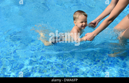 baby with her mother in the swimming pool - Stock Photo