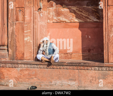 Local Indian Muslim man sitting cross legged in an alcove in the Jama Masjid Mosque, Old Delhi, India - Stock Photo