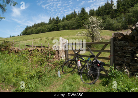Bicycle resting against a field gate on a roadside near Coniston in the English Lake District - Stock Photo