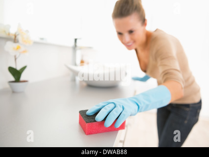 Closeup on young woman cleaning desk in bathroom - Stock Photo