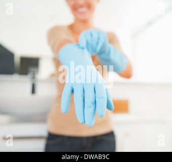 Closeup on housewife wearing gloves - Stock Photo