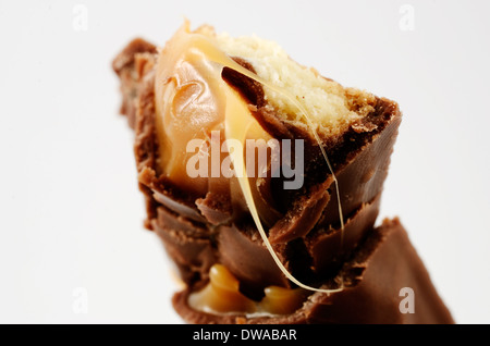 half a chocolate bar with caramel on white background - Stock Photo
