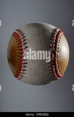 dirty baseball, white and brown on a gray background, close-up - Stock Photo