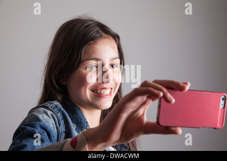 Teenage girl making a video call on her mobile phone - Stock Photo