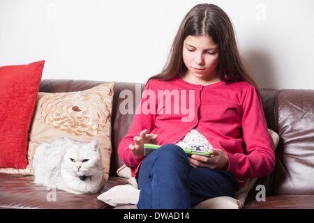 Teenage girl browsing the Internet on a tablet - Stock Photo