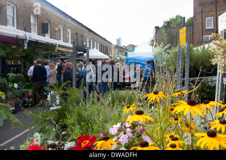 Columbia Road Flower Market Bethnal Green London England UK Flowers on stall in foreground people browsing in background - Stock Photo