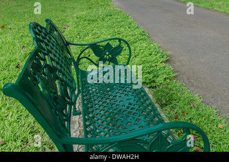 Green bench in park on grass near walkway - Stock Photo