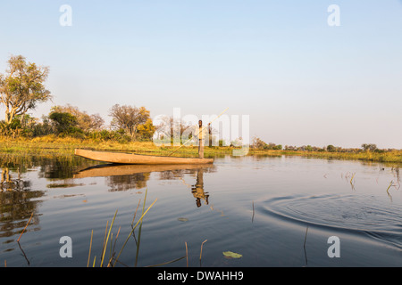 Peaceful mokoro boat with guide on river with reflections at Xigera Camp in the Okavango Delta, Botswana, southern - Stock Photo