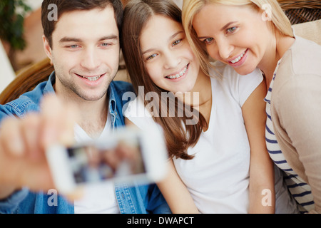 Young man holding cellular phone with happy daughter and wife near by - Stock Photo