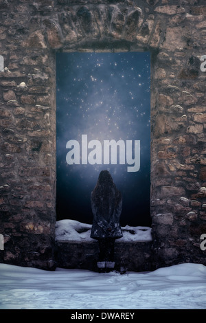 a girl is standing in front of a window of an old castle in the snow - Stock Photo