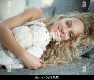 Portrait of young woman with teddy bear lying on sofa - Stock Photo