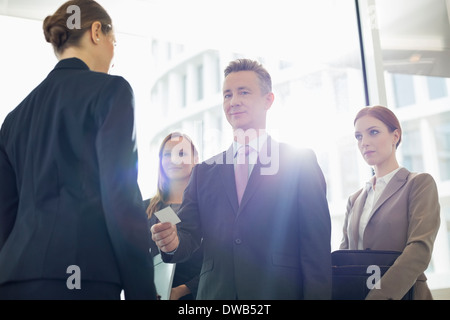 Portrait of businessman giving his card to businesswoman in office - Stock Photo