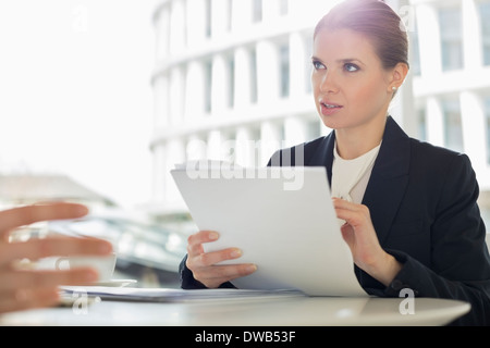 Businesswoman discussion paperwork with colleague in office cafeteria - Stock Photo