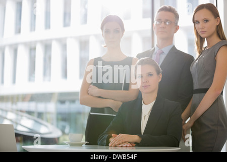 Portrait of confident business team in office cafeteria - Stock Photo