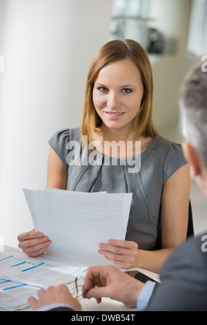 Portrait of beautiful businesswoman with documents in office cafeteria - Stock Photo