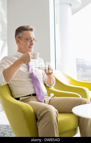 Mature businessman having coffee in lobby at office - Stock Photo
