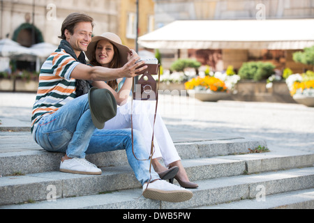 Tourist couple photographing on steps - Stock Photo