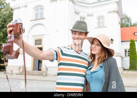 Tourist couple taking self portrait outside St. Casimir Church, Warsaw, Poland - Stock Photo
