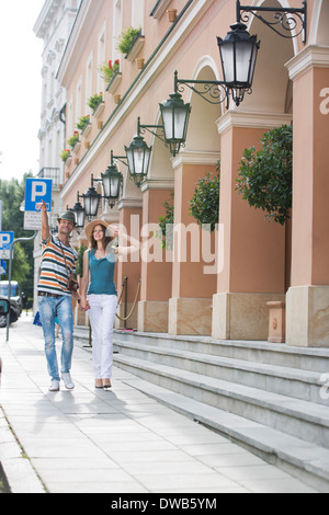 Tourist couple walking on sidewalk along building - Stock Photo