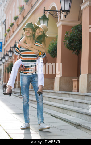 Young man giving piggyback ride to woman on sidewalk by building - Stock Photo