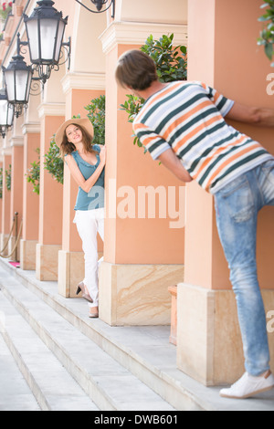 Tourist couple playing hide-and-seek amongst columns - Stock Photo