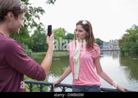 Young man photographing woman through cell phone at lakeside - Stock Photo