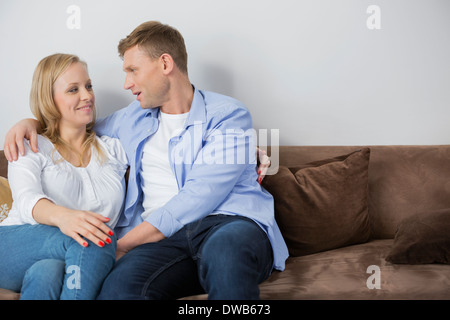 Loving mid adult couple sitting on sofa at home - Stock Photo