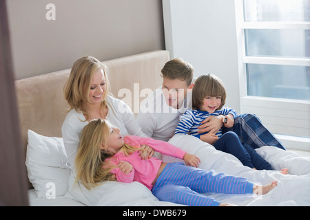Parents playing with children in bedroom - Stock Photo