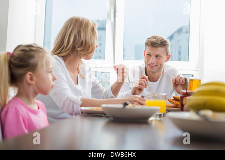 Happy family of three having breakfast at table - Stock Photo