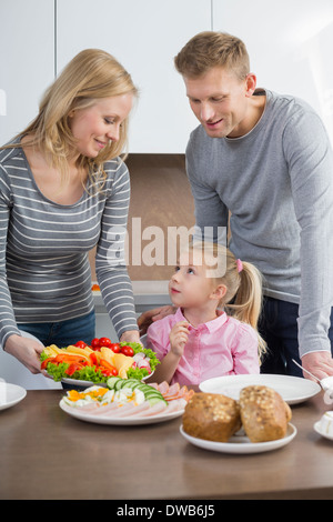 Happy parents with daughter having meal in kitchen - Stock Photo