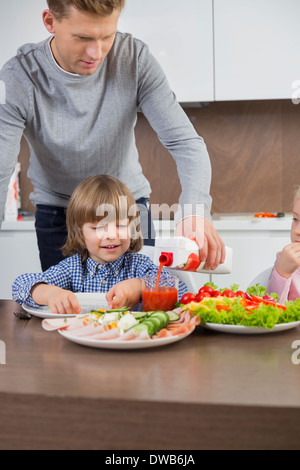 Father pouring juice for son at table in kitchen - Stock Photo