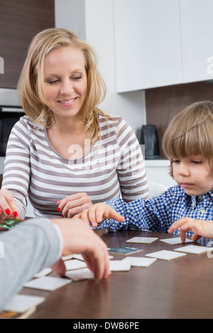 Boy playing cards with parents at home - Stock Photo