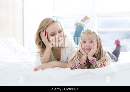Mother looking at cute daughter making faces while lying in bed - Stock Photo