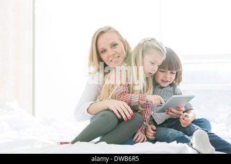 Portrait of happy mother with children using digital tablet in bedroom - Stock Photo