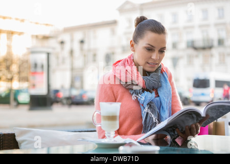 Young woman reading book at sidewalk cafe - Stock Photo