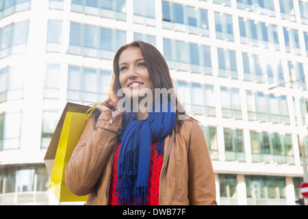 Thoughtful young woman carrying shopping bags in winter - Stock Photo