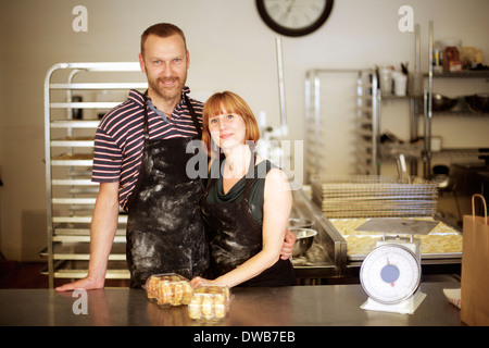Portrait of baker couple behind kitchen counter - Stock Photo