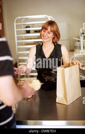 Female baker serving customer in bakery - Stock Photo